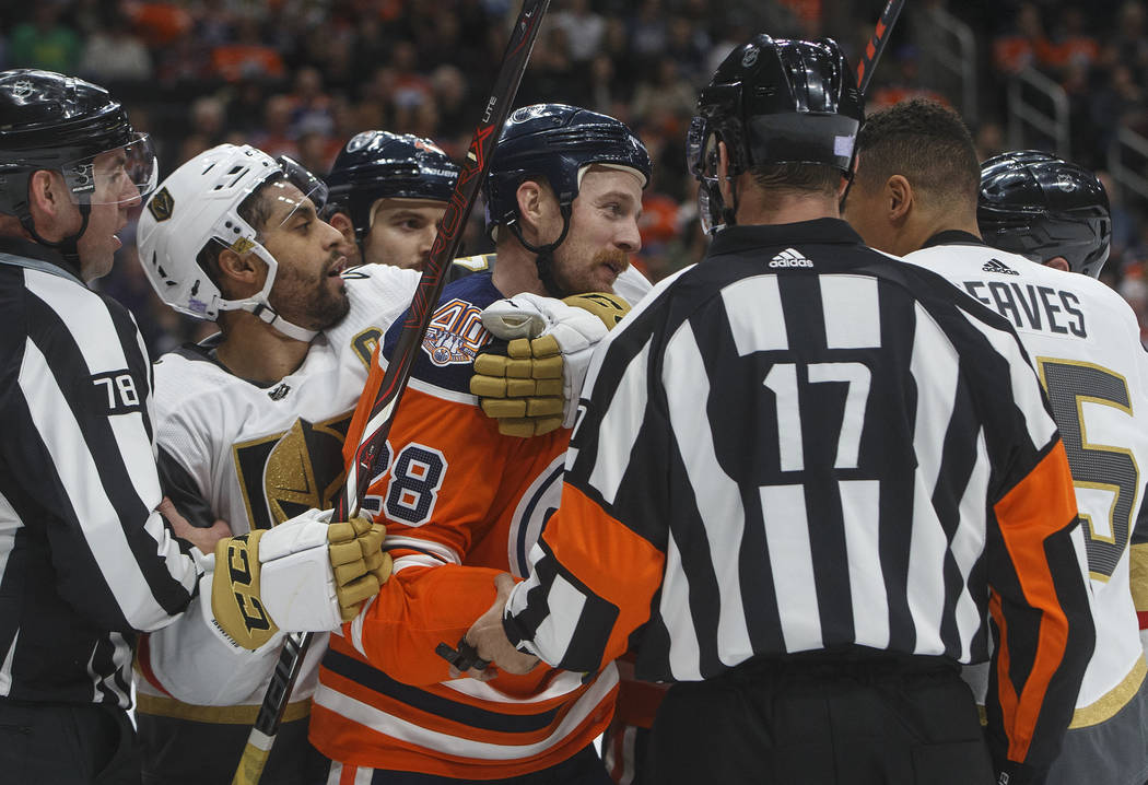 Vegas Golden Knights' Pierre-Edouard Bellemare (41) holds back Edmonton Oilers' Kyle Brodziak (28) as he goes after Ryan Reaves (75) during the first period of an NHL hockey game Sunday, Nov. 18, ...