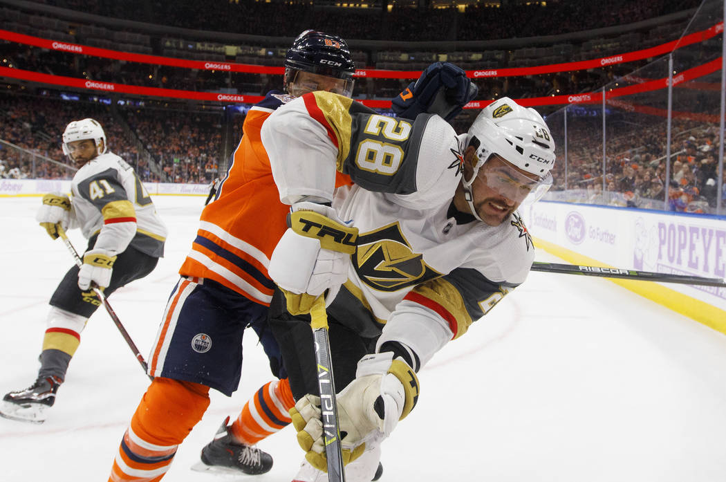 Vegas Golden Knights' William Carrier (28) and Edmonton Oilers' Matthew Benning battle in the corner during the third period of an NHL hockey game Sunday, Nov. 18, 2018, in Edmonton, Alberta. (Jas ...