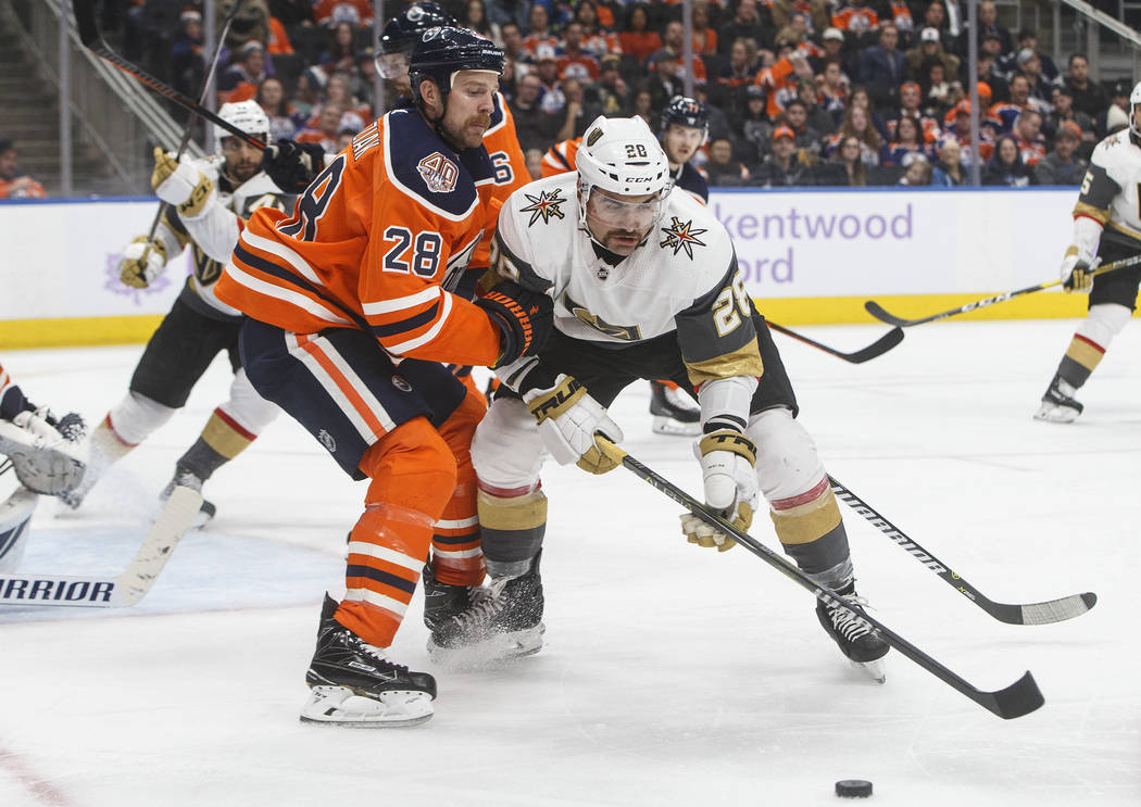Vegas Golden Knights' William Carrier (28) and Edmonton Oilers' Kyle Brodziak (28) compete for the puck during the third period of an NHL hockey game Sunday, Nov. 18, 2018, in Edmonton, Alberta. ( ...