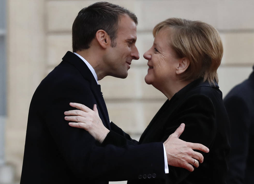 FILE - In this Nov. 11, 2018 file photo, French President Emmanuel Macron hugs German Chancellor Angela Merkel in the courtyard of the Elysee Palace in Paris while marking the 100th anniversary of ...