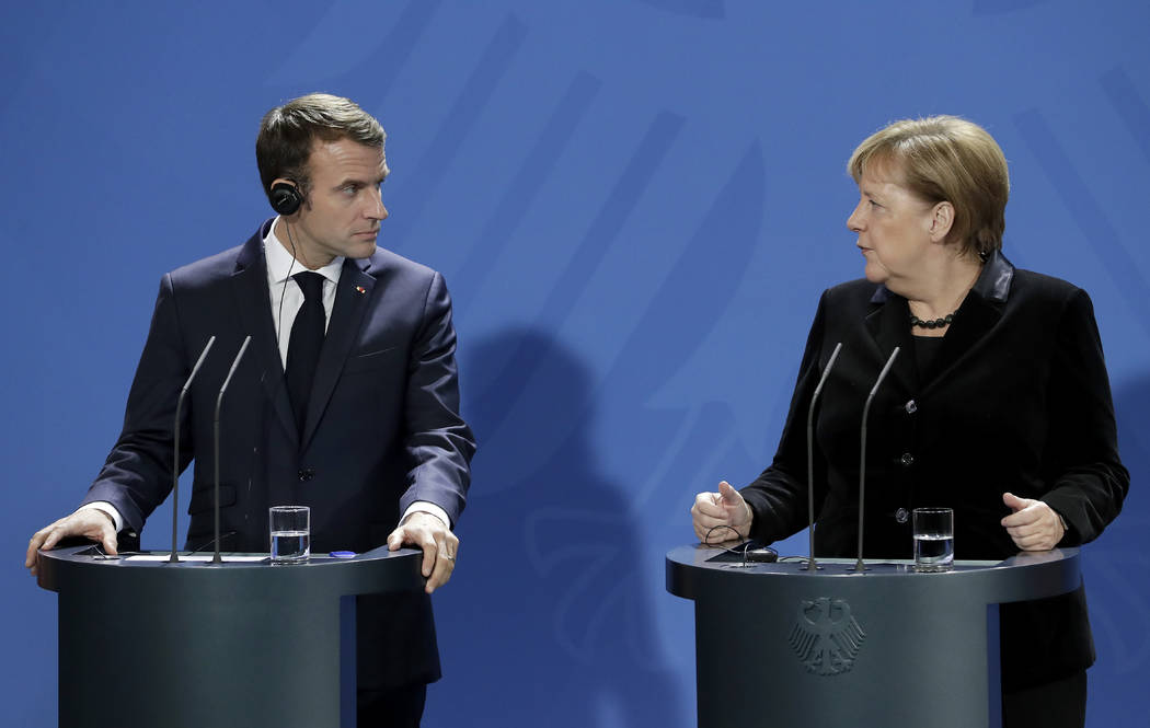 German Chancellor Angela Merkel, right, and France's President Emmanuel Macron, left, address the media during a joint statement prior to a meeting at the chancellery in Berlin, Germany, Sunday, N ...