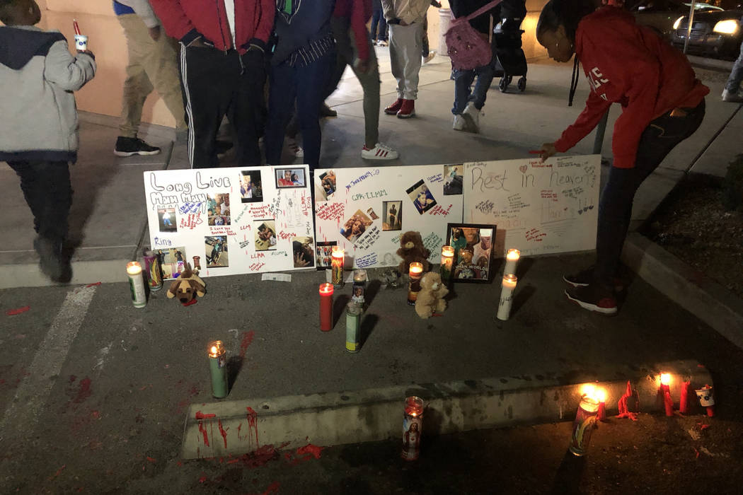 A woman adjusts posters remembering LaMadre Harris during a vigil Nov. 14. The 16-year-old boy died after a shooting in North Las Vegas on Tuesday, Nov. 13, 2018, his mother said. (Katelyn Newberg ...