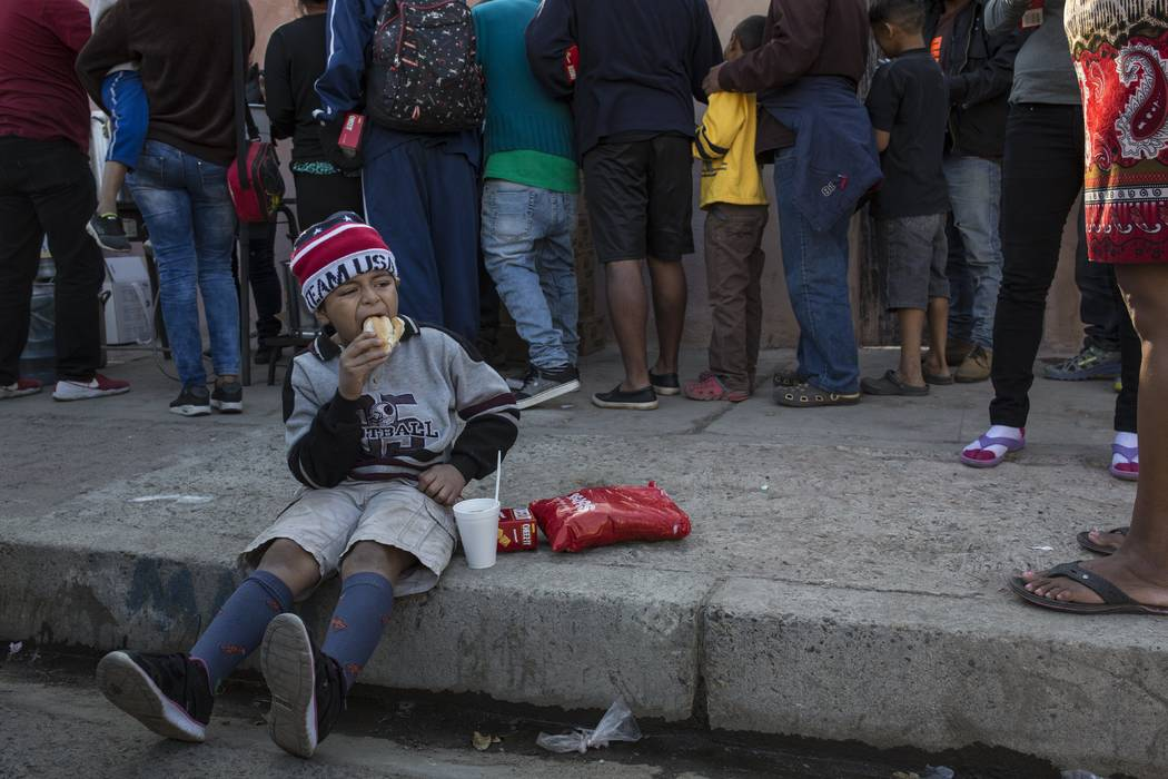A Central American migrant boy eats a donated breakfast at a temporary shelter in Tijuana, Mexico, early Saturday morning, Nov. 17, 2018. Many of the nearly 3,000 migrants have reached the border ...