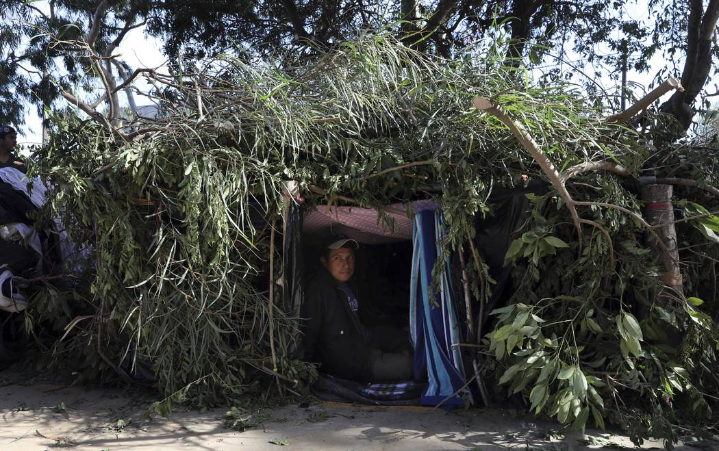 Honduran migrant Mauro Hernandez rests inside a makeshift tent at a temporary shelter in Tijuana, Mexico, early Saturday morning, Nov. 17, 2018. Many of the nearly 3,000 migrants have reached the ...