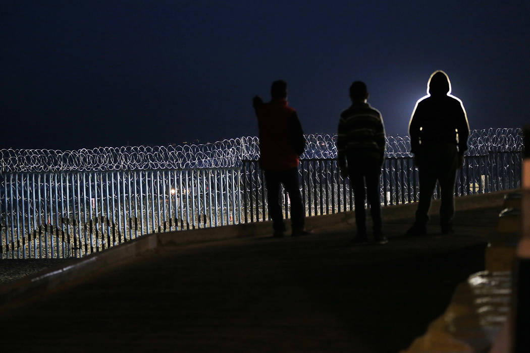 Residents stand on a hill before barriers, wrapped in concertina wire, separating Mexico and the United States, where the border meets the Pacific Ocean, in Tijuana, Mexico, Saturday, Nov. 17, 201 ...