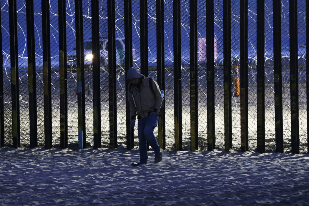 A resident walks near barriers, wrapped in concertina wire, separating Mexico and the United States, where the border meets the Pacific Ocean, in Tijuana, Mexico, Saturday, Nov. 17, 2018. Many of ...