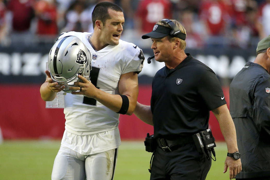 Oakland Raiders quarterback Derek Carr (4) talks with head coach Jon Gruden during the second half of an NFL football game against the Arizona Cardinals , Sunday, Nov. 18, 2018, in Glendale, Ariz. ...