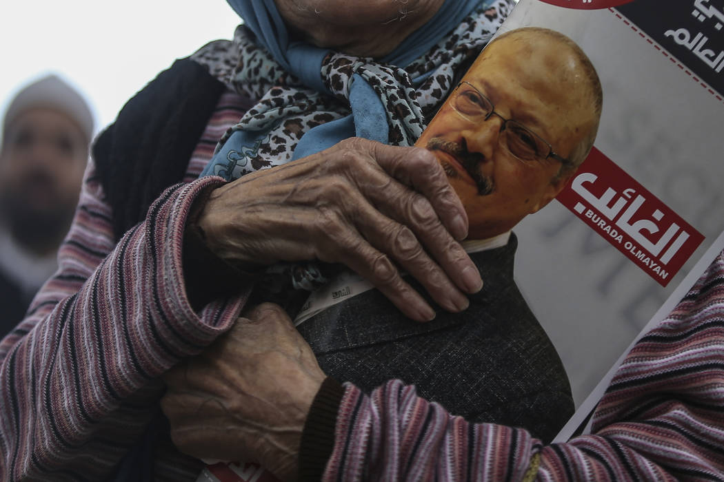 A woman holds a poster during the funeral prayers in absentia for Saudi writer Jamal Khashoggi who was killed last month in the Saudi Arabia consulate, in Istanbul, Friday, Nov. 16, 2018. Turkey's ...