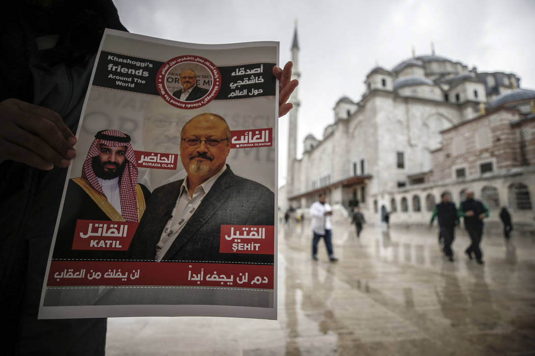 "A man holds a poster showing images of Saudi Crown Prince Muhammed bin Salman and of journalist writer Jamal Khashoggi, describing the prince as ""assassin"" and Khashoggi as ""martyr& ..."