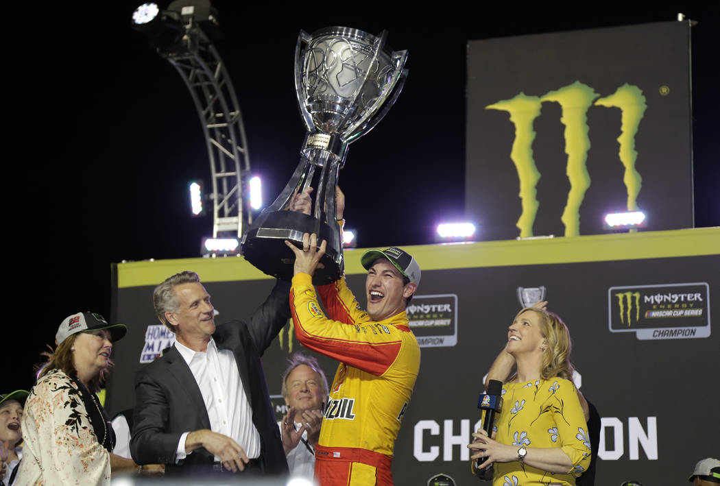 Joey Logano, second from right, holds the trophy with Steve Phelps, president of NASCAR after winning the Cup Series Championship auto race at the Homestead-Miami Speedway, Sunday, Nov. 18, 2018, ...