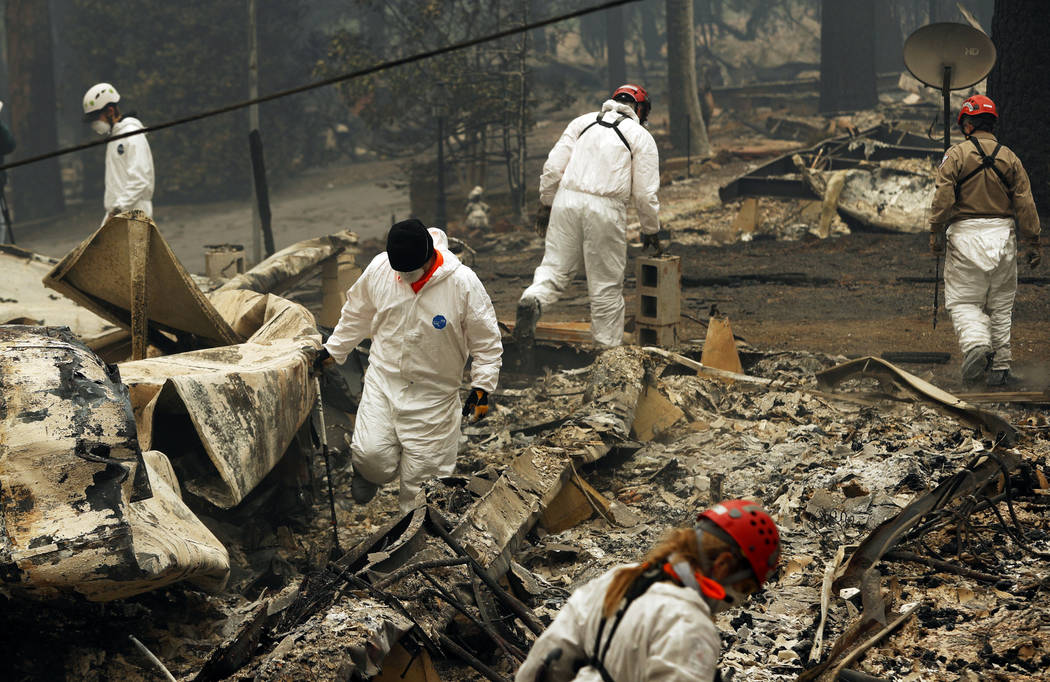 In this Tuesday, Nov. 13, 2018 photo, search and rescue workers search for human remains at a trailer park burned out from the Camp fire in Paradise, Calif. (AP Photo/John Locher)