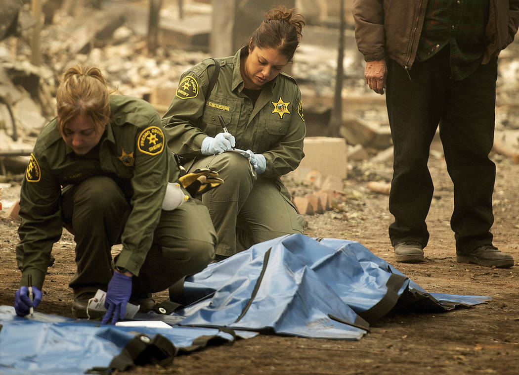 In this Wednesday, Nov. 14, 2018, photo, Sheriff's deputies recover the bodies of multiple Camp fire victims at the Holly Hills Mobile Estates residence in Paradise, Calif. (AP Photo/Noah Berger)