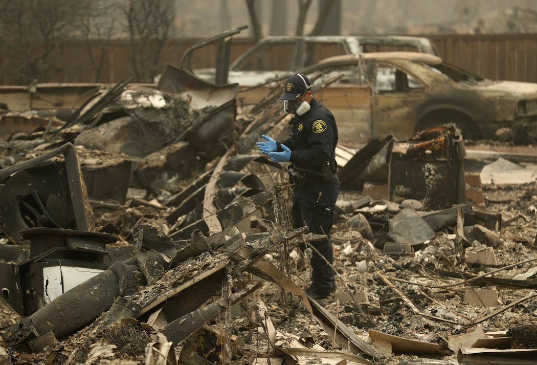 In this Thursday, Nov. 15, 2018 photo, a Sheriff's deputy looks for human remains at a home burned in the Camp fire in Magalia, Calif. (AP Photo/John Locher, File)