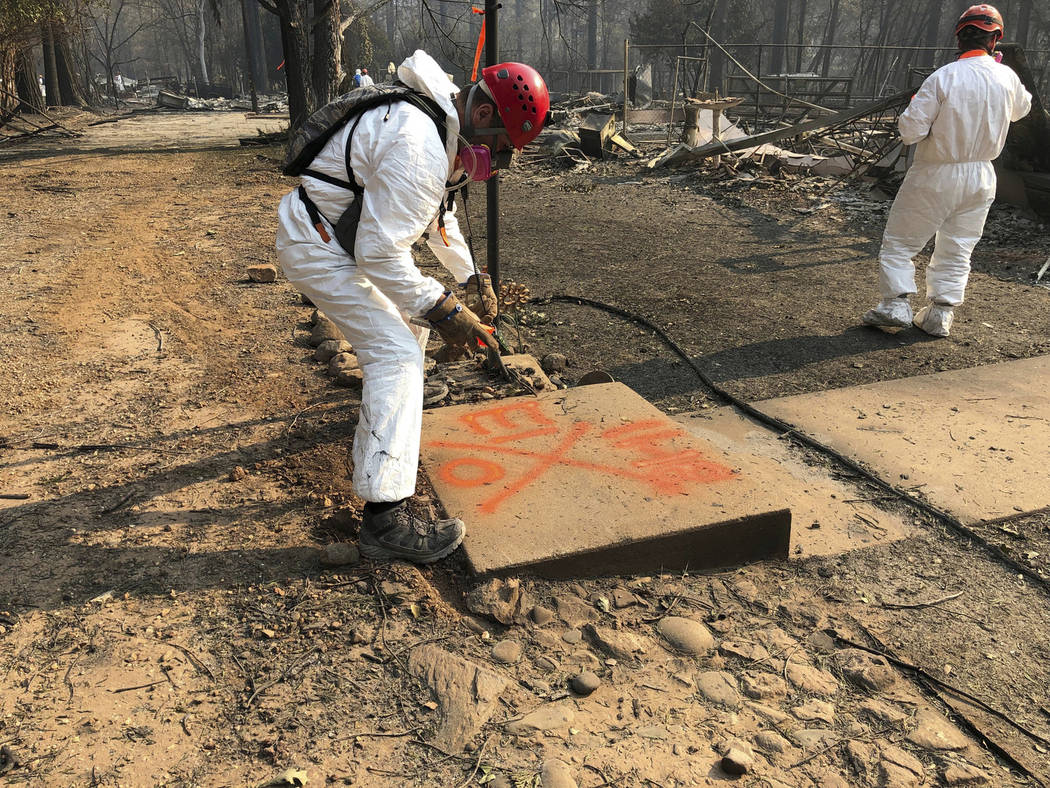 A volunteer member of an El Dorado County search and rescue team uses orange spray paint to mark the ruins of a home to show that no human remains were found at the location in Paradise, Calif., S ...