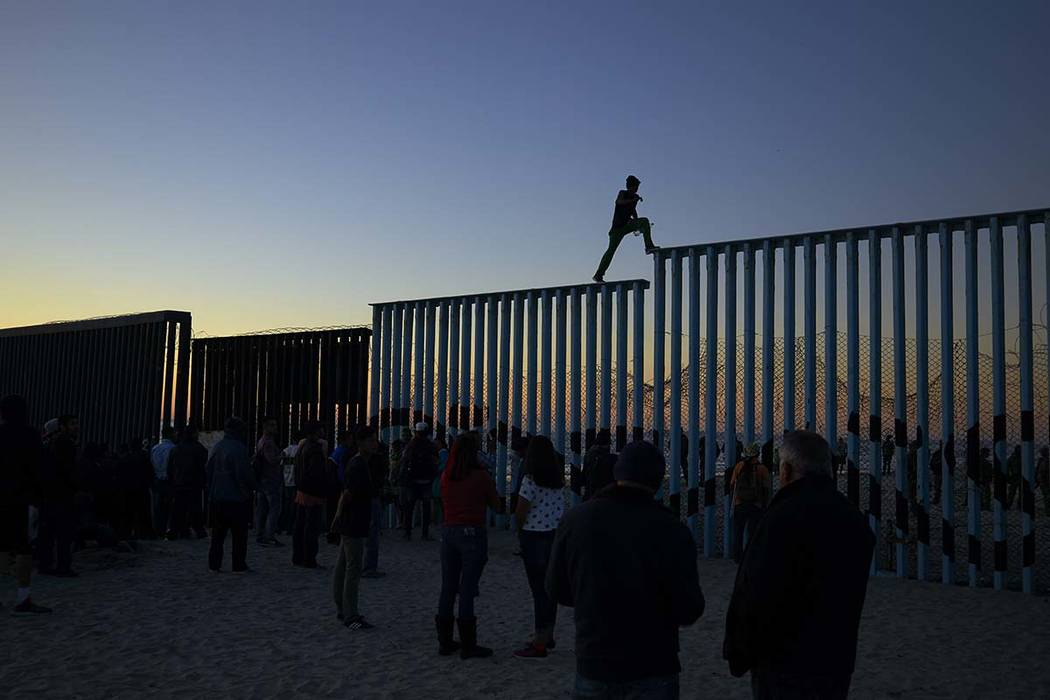 In this Nov. 14, 2018 picture, a man from Honduras walks along the top of the border structure separating Mexico and the United States, in Tijuana, Mexico. With about 3,000 Central American migran ...
