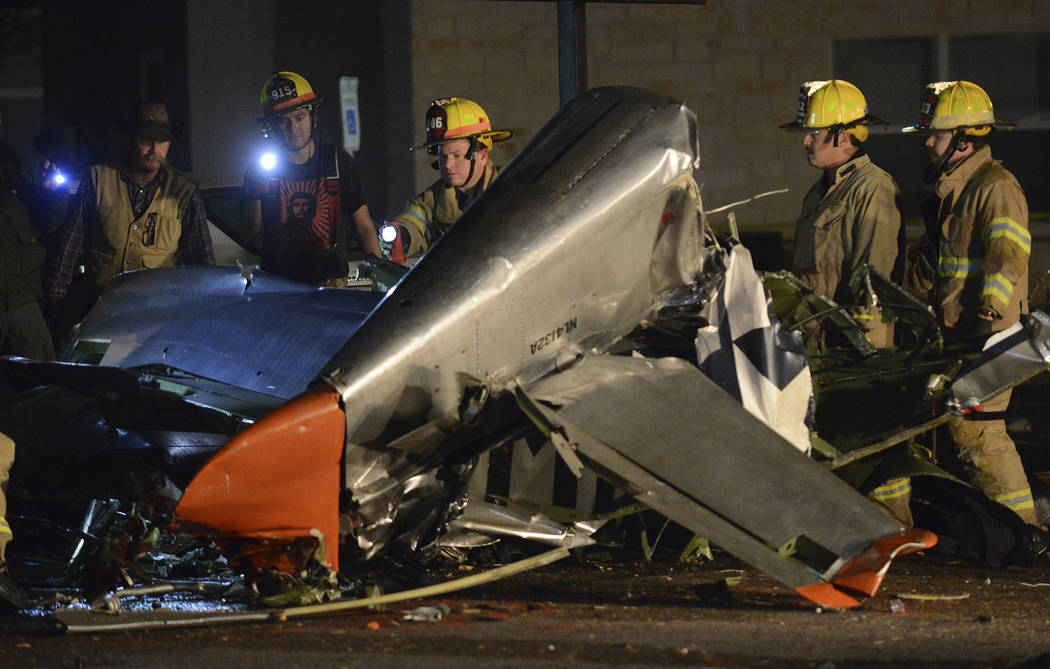 In this Saturday, Nov. 17, 2018, photo firefighters and investigators look over a vintage World War II P-51D Mustang aircraft after a deadly crash in Fredericksburg, Texas. (Billy Calzada/The San ...