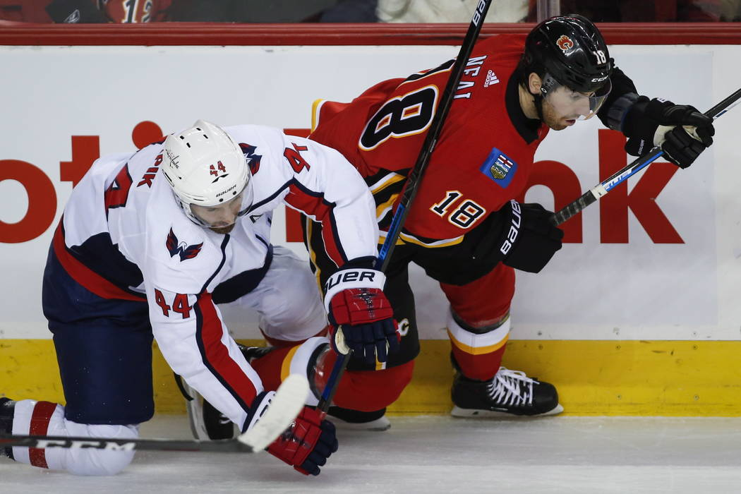 Washington Capitals' Brooks Orpik, left, checks Calgary Flames' James Neal during first-period NHL hockey game action in Calgary, Alberta, Saturday, Oct. 27, 2018. (Jeff McIntosh/The Canadian Pres ...