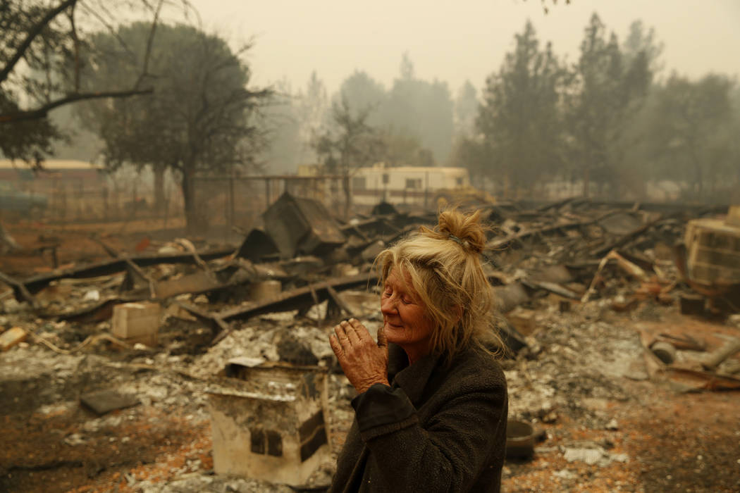 """FILE - In this Nov. 9, 2018 photo, Cathy Fallon reacts as she stands near the charred remains of her home in Paradise, Calif. """"I'll be darned if I'm gonna let those horses burn in the fire&qu ..."""