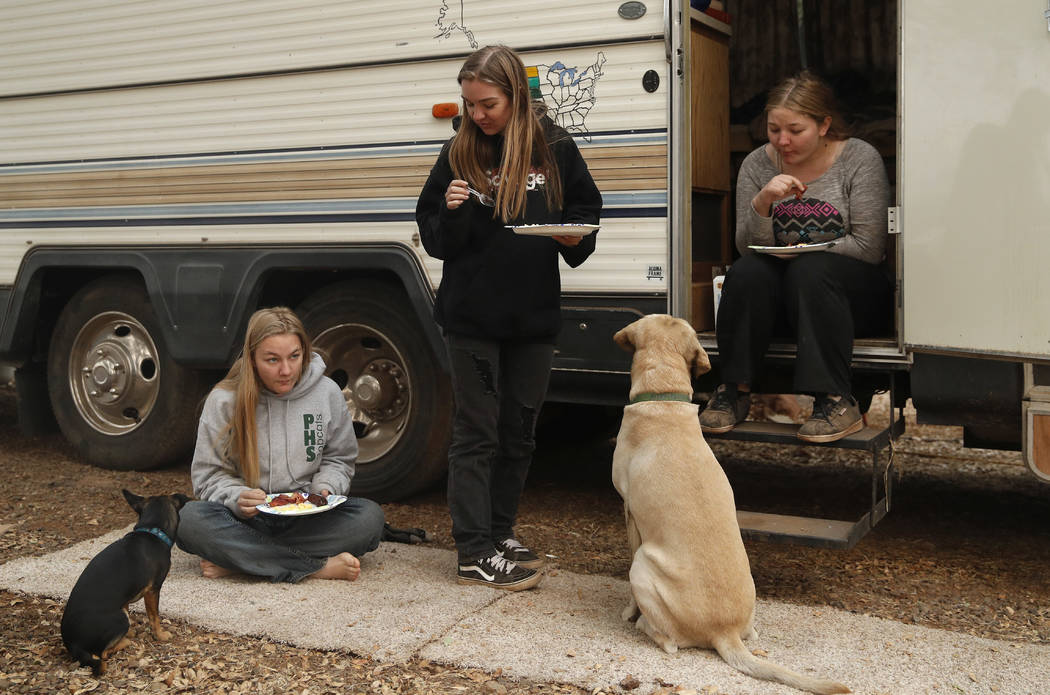 In this Nov. 14, 2018, photo, sisters Arissa Harvey, from left, Araya Cipollini, and Arianne Harvey eat beside an RV they are living in near their home was destroyed in the Camp Fire in Paradise, ...