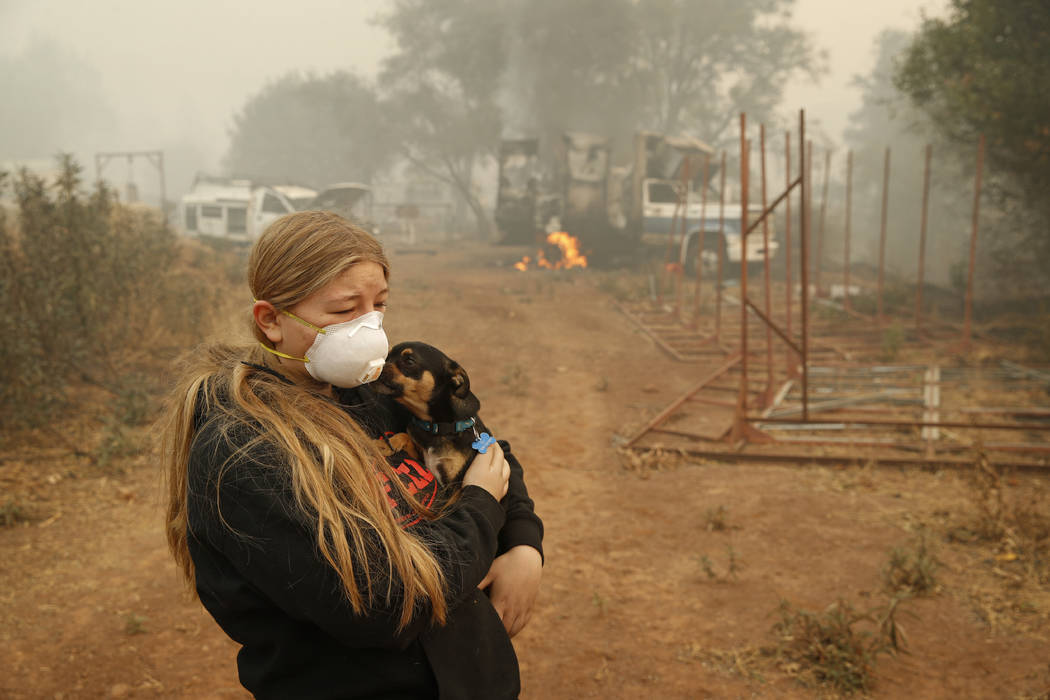 In this Nov. 10, 2018, photo, Arianne Harvey holds her dog T.J. near a truck still on fire from the Camp Fire in Paradise, Calif. Harvey was living in an RV near where her family's home was destro ...