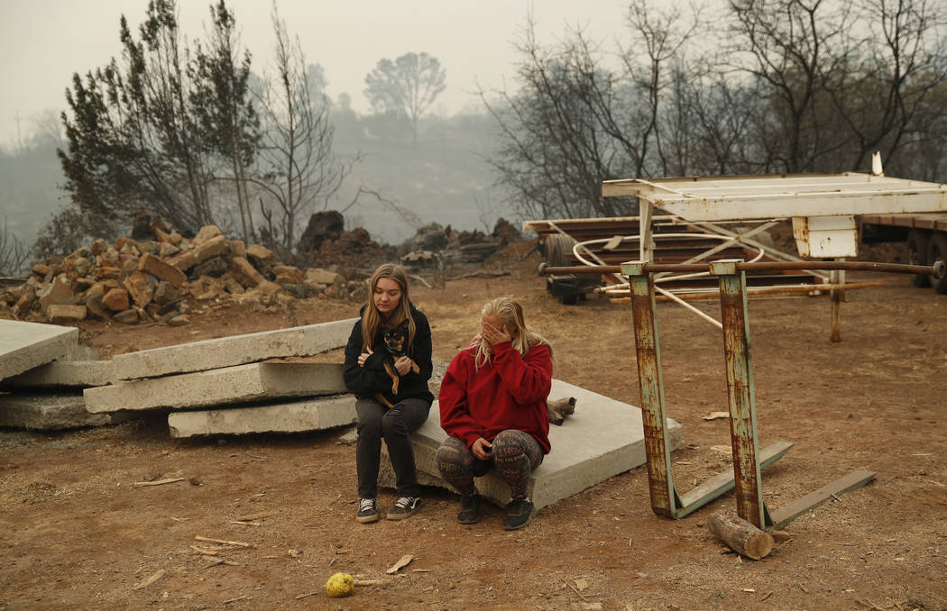 In this Nov. 14, 2018, photo, Krystin Harvey, right, and her daughter Araya Cipollini rest on property near the location of their home that was destroyed in the Camp Fire in Paradise, Calif. &quot ...