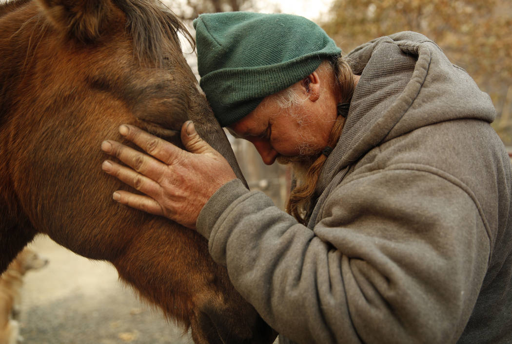 """In this Nov. 15, 2018, photo, Troy Miller rubs his horse Sally at his burned out property in Concow, Calif. """"I've got a lot of faith in God. I think things will be OK,"""" said Miller. &quo ..."""