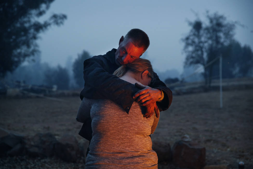 In this Nov. 14, 2018, photo, Phillip Harvey embraces his daughter Arianne Harvey as they stay warm beside a fire in Paradise, Calif. The family lost their home in the Camp Fire and were living in ...