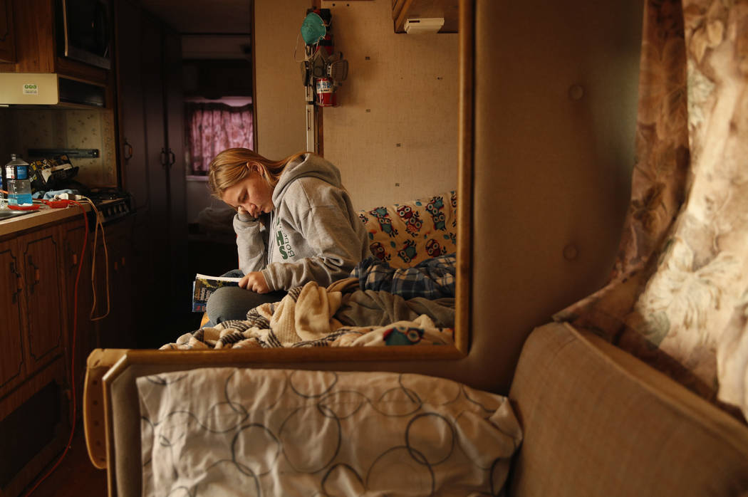 In this Nov. 14, 2018, photo, 16-year-old Arissa Harvey studies a chemistry book in an RV where she is living with her family in Paradise, Calif. Harvey's family home was destroyed in the Camp Fir ...