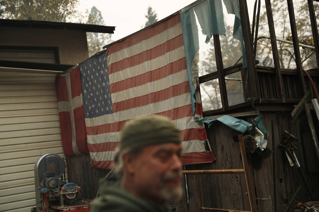 In this Nov. 15, 2018, photo, Brad Weldon stands near flags adorning his home in Paradise, Calif. Weldon, who saved his Paradise home from the fire, says there was nowhere he could take his 89-yea ...