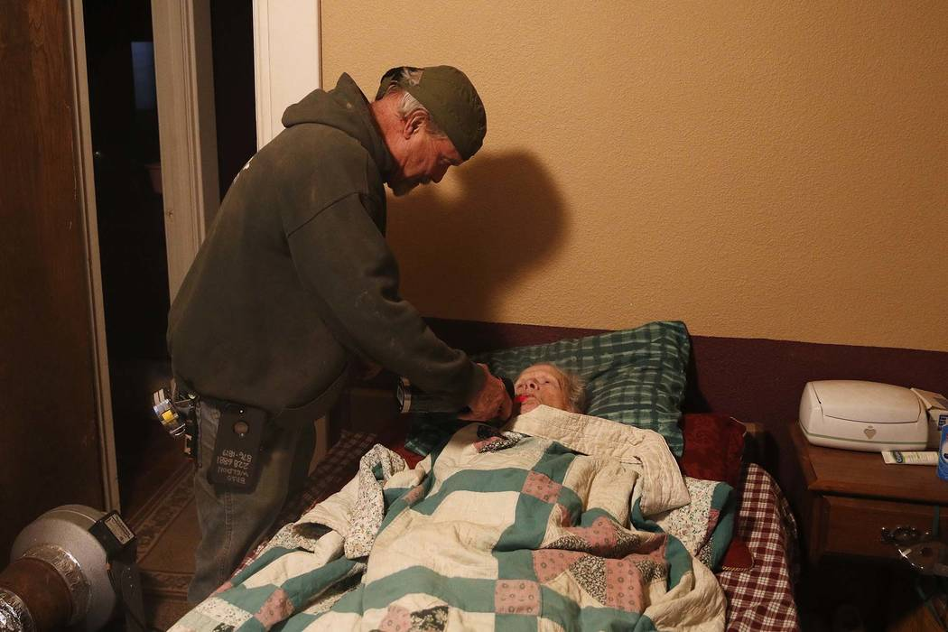 In this Nov. 15, 2018, photo, Brad Weldon gives his 89-year-old mother Norma Weldon a drink at their home in Paradise, Calif. Weldon, who saved his Paradise home from the fire, says there was nowh ...