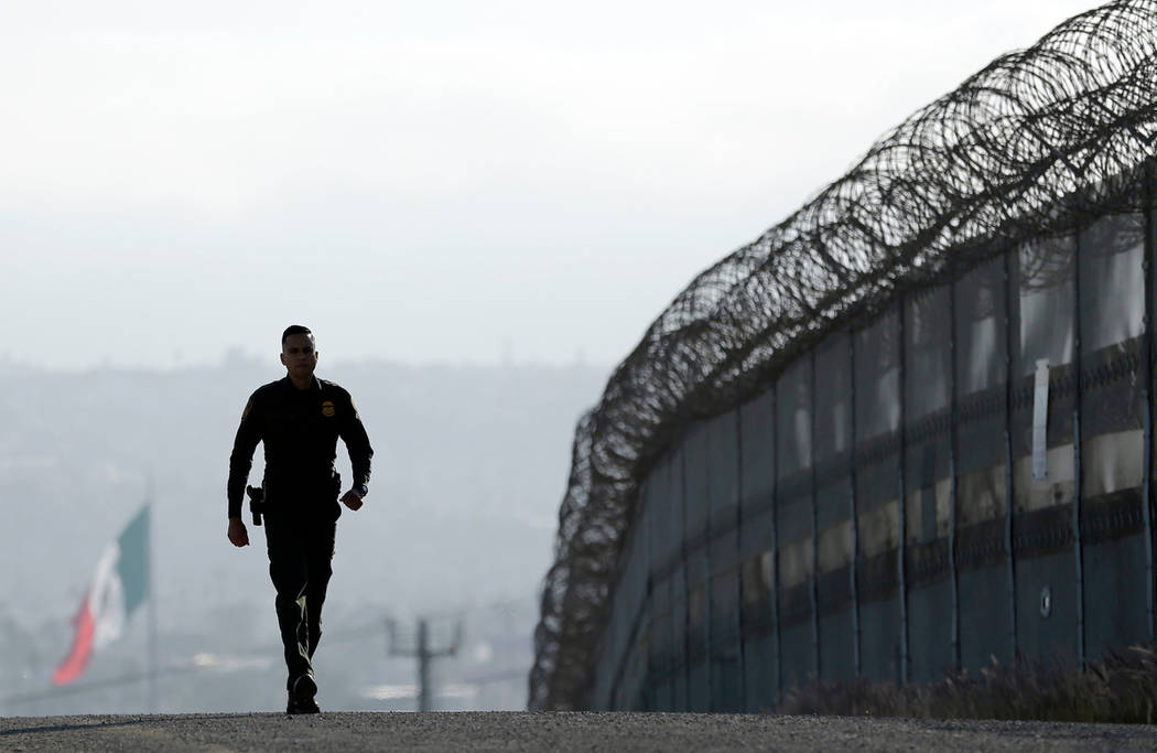 In this June 22, 2016 file photo, Border Patrol agent Eduardo Olmos walks near the secondary fence separating Tijuana, Mexico, background, and San Diego in San Diego. In his threat Tuesday, April ...