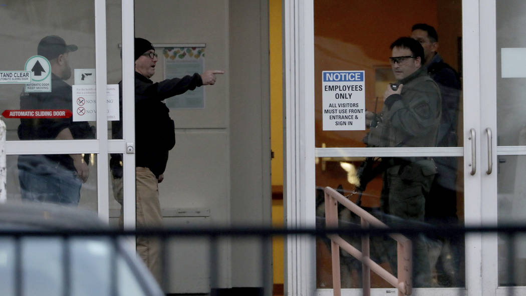 Law enforcement officers including Chicago SWAT work an entrance at Mercy Hospital Monday, Nov. 19, 2018, in Chicago. A shooting at a Chicago hospital has wounded multiple people, including a susp ...