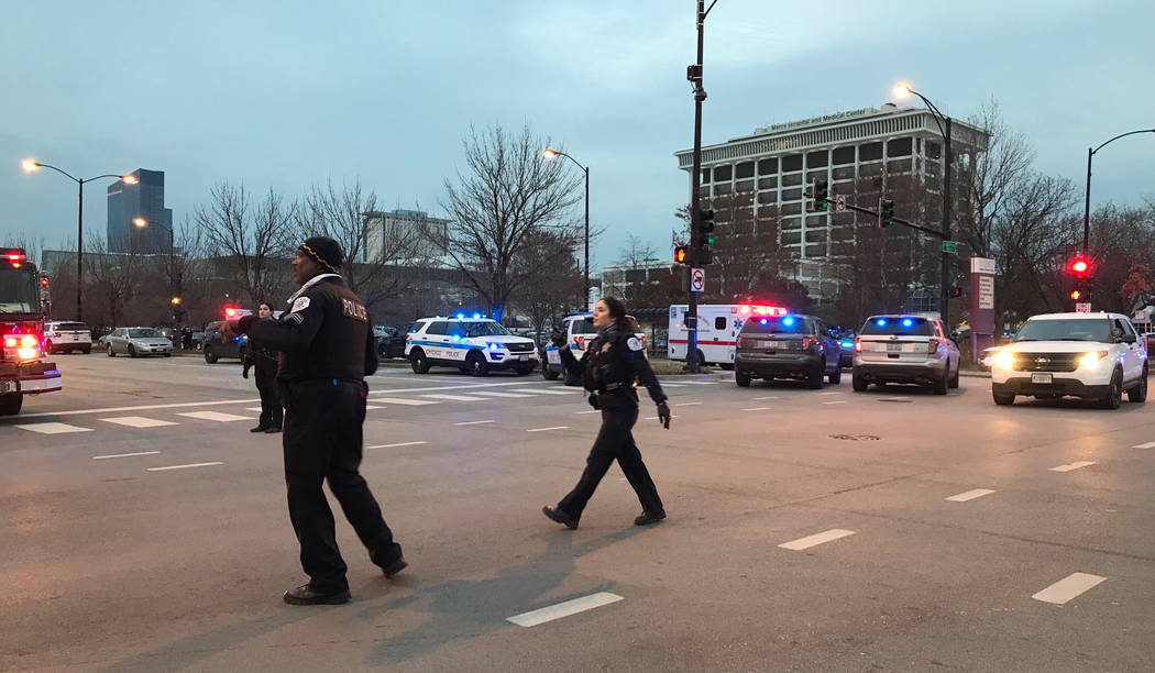 Chicago Police officers walk outside Mercy Hospital on the city's South Side where authorities say a shooting at the hospital has wounded multiple people, including a suspect and a police officer, ...