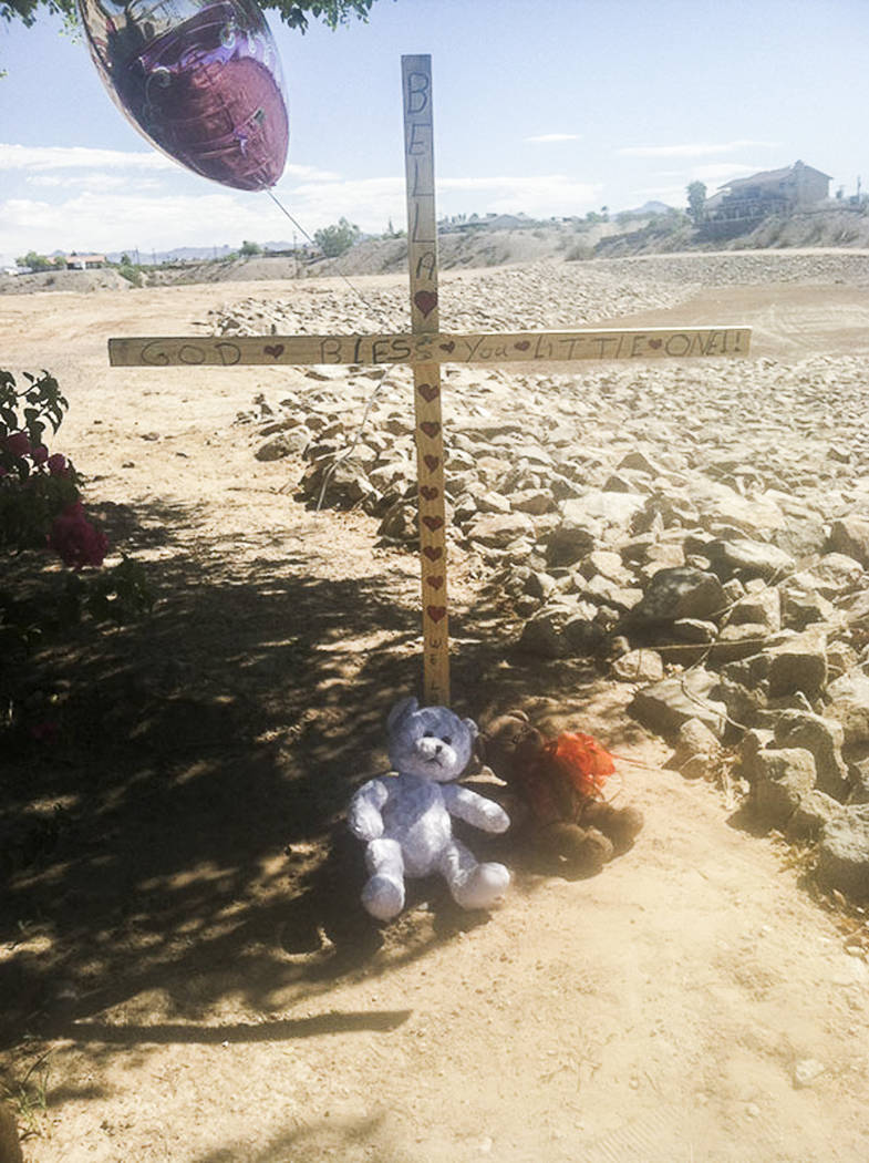 A marker with balloons and stuffed toys are near the lot at Chaparral and Country Club drives in Bullhead City, Arizona, where the body believed to be 8-year-old Isabella Grogan-Cannella was found ...