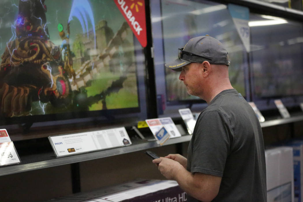 Rich Sigle checks pricing on LED TVs at Walmart just before the holiday shopping season begins on Tuesday, Nov. 20, 2018. (Michael Quine/Las Vegas Review-Journal) @Vegas88s