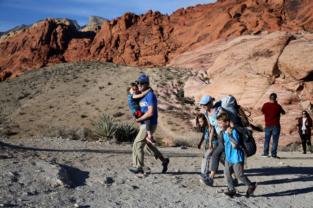 Matt Arentz of Seattle carries his daughter Cassie Meier-Arentz, 5, while his wife, Cindy Meier, walks with Adi Meier-Arentz, 8, and Jackson Meier-Arentz, 9, after the family went rock climbing in ...