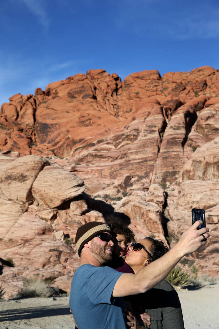 David and Rebekah Wendlek of Bend, Ore. take a photo with their daughter Mia Rose Wendlek, 3, near the Calico 1 parking area on the Scenic Loop in Red Rock Canyon Nation Conservation Area Tuesday, ...