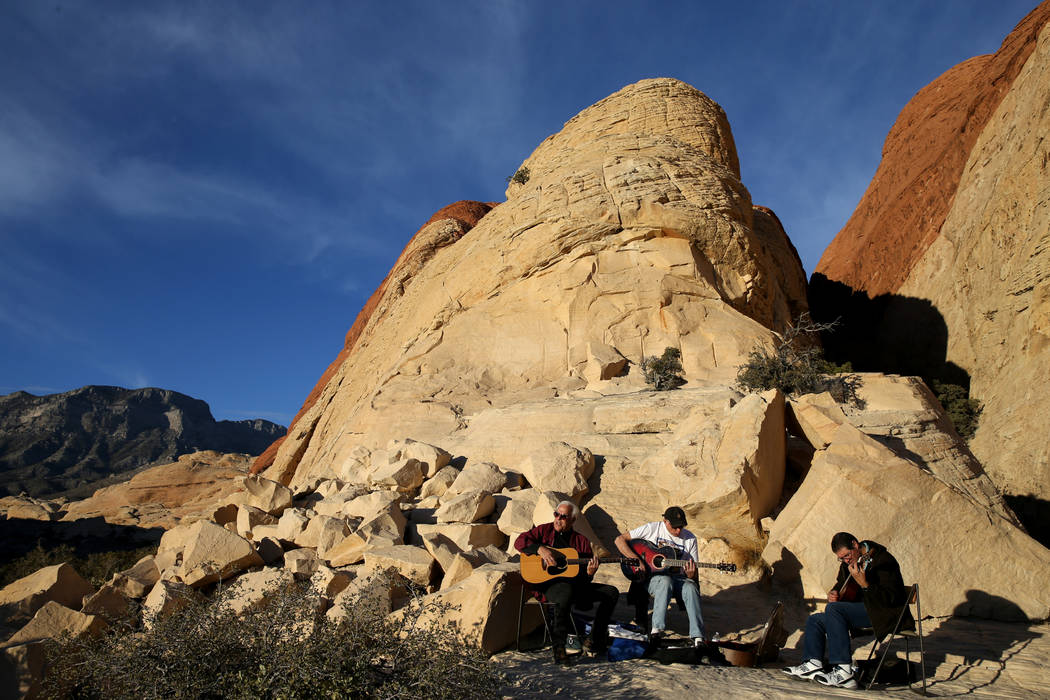 "Phil ""Fang"" Volk of Las Vegas, from left, Gary Howell of Las Vegas and John Schilling of Washington D.C. play music near the Sandstone Quarry parking area on the Scenic Loop in Red Rock ..."