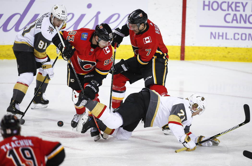Vegas Golden Knights' William Karlsson, right, of Sweden, is knocked to the ice as teammate Jonathan Marchessault, left, and Calgary Flames' Sam Bennett, center, and T.J. Brodie scramble for the p ...