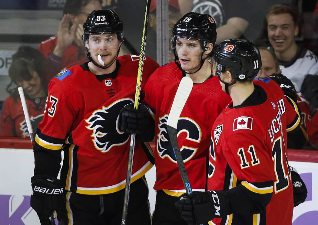 Calgary Flames' Matthew Tkachuk, centere, celebrates his goal with teammates Sam Bennett, left, and Mikael Backlund, of Sweden, during second-period NHL hockey game action against the Vegas Golden ...