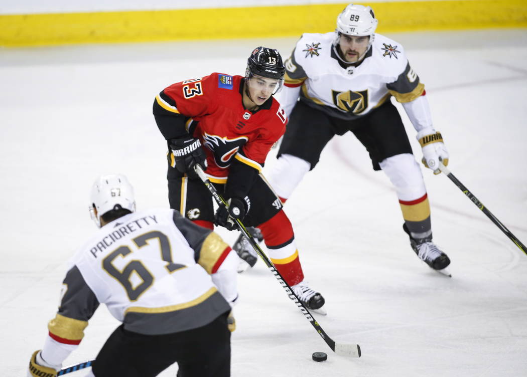 Calgary Flames' Johnny Gaudreau, centre, skates between Vegas Golden Knights' Max Pacioretty, left, and Alex Tuch during second period NHL hockey action in Calgary, Alberta, Monday, Nov. 19, 2018. ...