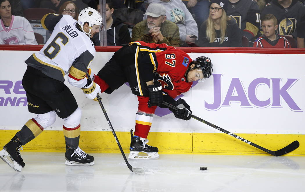 Vegas Golden Knights' Colin Miller, left, checks Calgary Flames' Michael Frolik, of the Czech Republic, into the boards during third period NHL hockey action in Calgary, Alberta, Monday, Nov. 19, ...