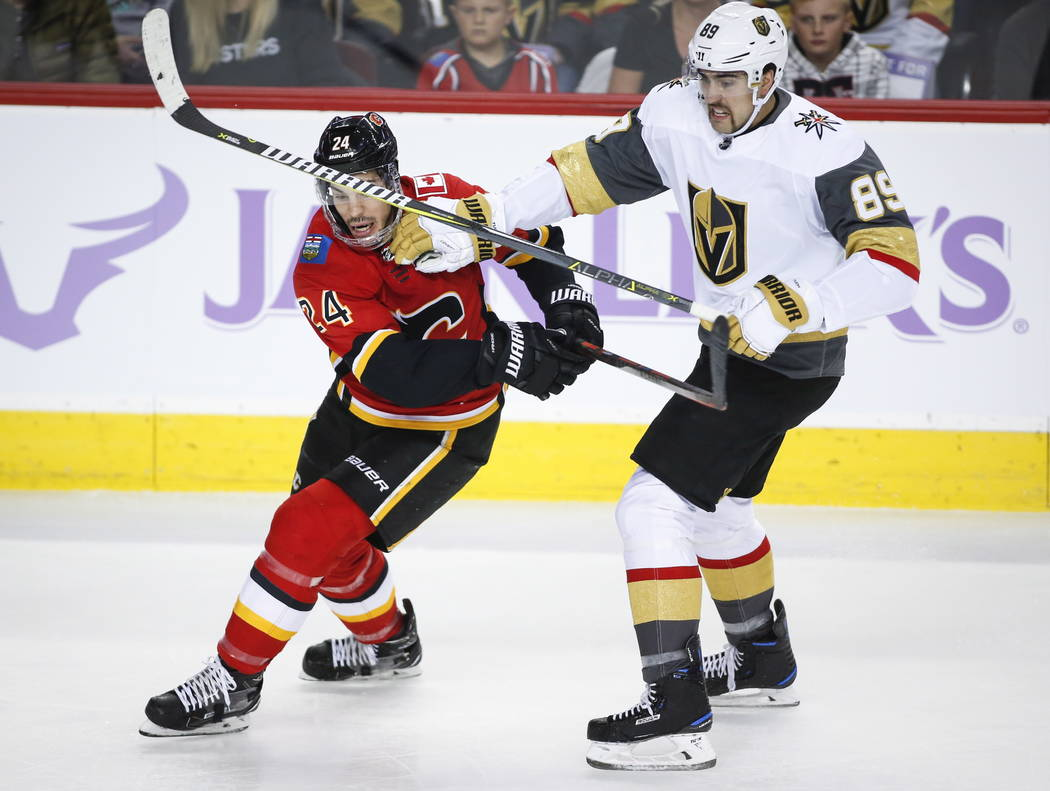 Vegas Golden Knights' Alex Tuch, right, checks Calgary Flames' Travis Hamonic during first-period NHL hockey game action in Calgary, Alberta, Monday, Nov. 19, 2018. (Jeff McIntosh/The Canadian Pre ...