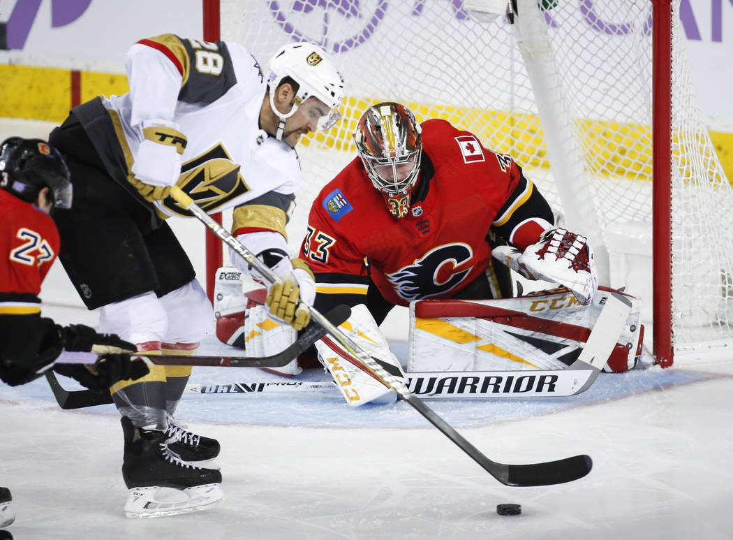 Vegas Golden Knights' William Carrier, left, tries to get the puck past Calgary Flames goalie David Rittich, of the Czech Republic, during first period NHL hockey action in Calgary, Alberta, Monda ...