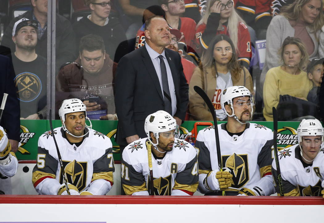 Vegas Golden Knights' head coach Gerard Gallant, top center, watches the action during second-period NHL hockey game action against the Calgary Flames in Calgary, Alberta, Monday, Nov. 19, 2018. ( ...