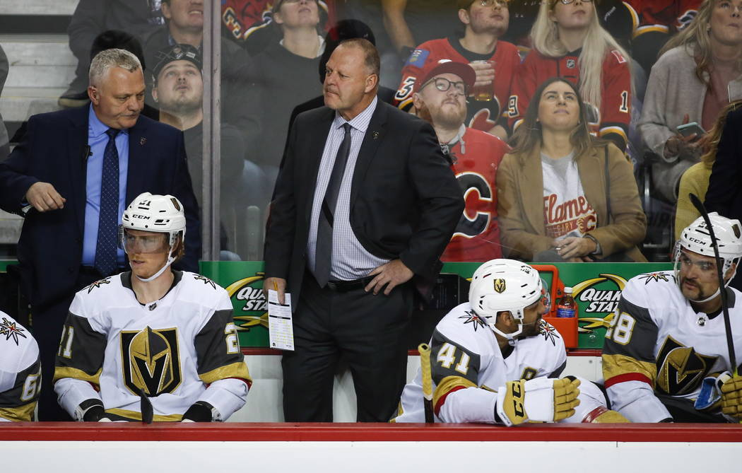 Vegas Golden Knights' head coach Gerard Gallant, center, watches the action during second-period NHL hockey game action against the Calgary Flames in Calgary, Alberta, Monday, Nov. 19, 2018. (Jeff ...