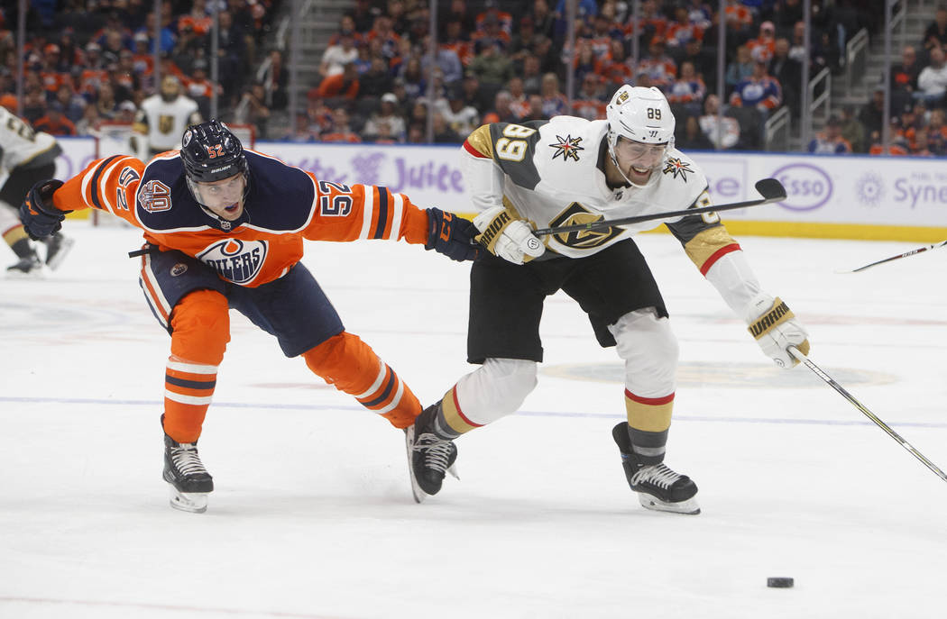 Vegas Golden Knights' Alex Tuch (89) and Edmonton Oilers' Patrick Russell (52) vie for the puck during the third period of an NHL hockey game Sunday, Nov. 18, 2018, in Edmonton, Alberta. (Jason Fr ...