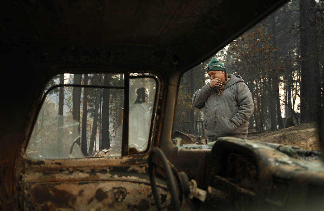 In this Nov. 15, 2018, photo, Troy Miller wipes his eyes as he walks beside a burned out car on his property in Concow, Calif. Miller said he tried to evacuate when the Camp Fire came roaring thro ...