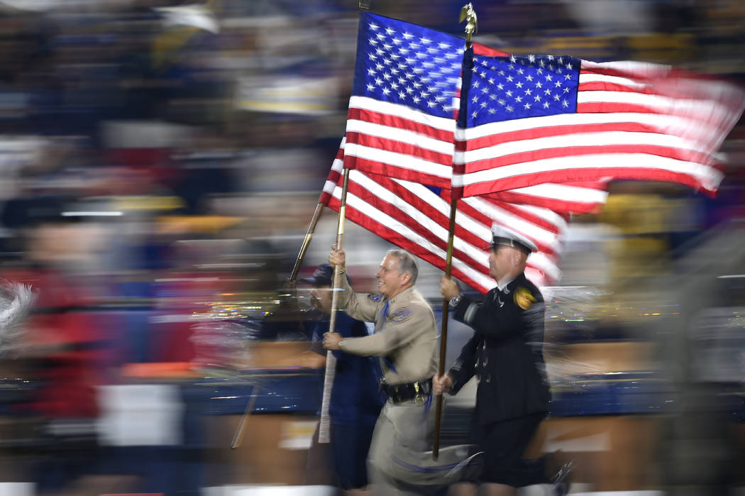 Fire and and law enforcement first responders run with United States flags as they lead players out of the tunnel before an NFL football game between the Los Angeles Rams and the Kansas City Chief ...