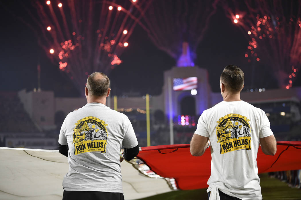 First responders hold the U.S. flag as fireworks go off before an NFL football game between the Los Angeles Rams and the Kansas City Chiefs at Los Angeles Memorial Coliseum, Monday, Nov. 19, 2018, ...